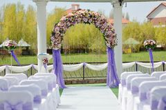 Wedding arch. Wedding arbor with a flower arch and white chairs Royalty Free Stock Photo