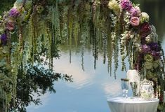 The wedding arch against the background of a water. Smooth surface decorated in flowers near her a little table with a ceremonial small pillow with wedding Stock Photography