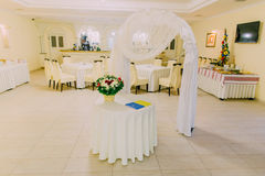Wedding arch in bright restaurant interior decorated and served for marriage celebration Royalty Free Stock Images
