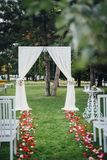 Wedding arch for the wedding ceremony, decorated with cloth and. Flowers on the green grass Royalty Free Stock Photos