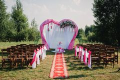 Wedding arch and chairs for ceremony decorated with white and pink flowers. Wedding arch and chairs for ceremony decorated with white and pink fabric and flowers Royalty Free Stock Image
