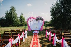 Wedding arch and chairs for guests for the ceremony decorated Royalty Free Stock Photography