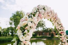 Wedding arch close-up decorated with flowers, white and pink roses and peonies on a pond background in the sunny summer. Wedding arch close-up decorated with Stock Photos