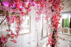 Wedding arch decorated with beautiful pink flowers. Wedding arch decorated with a lot of bright and beautiful pink flowers on the white indoors background Stock Photos