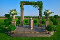 Wedding arch decorated with cloth and flowers outdoors. Beautiful wedding set up. Wedding ceremony on green lawn in the. Wedding arch decorated with flowers Royalty Free Stock Image