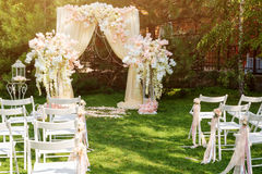 Wedding arch decorated with cloth and flowers outdoors. Beautiful wedding set up. Wedding ceremony on green lawn in the. Garden. Part of the festive decor Stock Photos