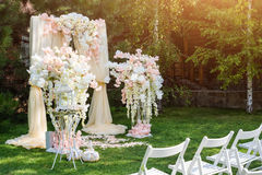 Wedding arch decorated with cloth and flowers outdoors. Beautiful wedding set up. Wedding ceremony on green lawn in the. Garden. Part of the festive decor Stock Images