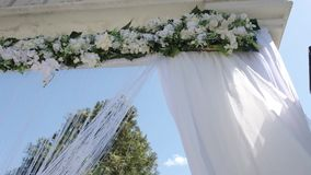 A wedding arch decorated with flowers and large wind-developing fabrics. Shooting in motion. stock footage