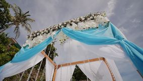 A wedding arch decorated with flowers and large wind-developing fabrics on a tropical beach. Philippines. Bohol. A wedding arch decorated with flowers and large stock video