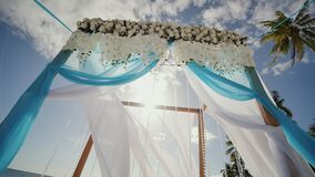 A wedding arch decorated with flowers and large wind-developing fabrics on a tropical beach. Philippines. Bohol. A wedding arch decorated with flowers and large stock video footage