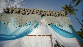 A wedding arch decorated with flowers and large wind-developing fabrics on a tropical beach. Philippines. Bohol. A wedding arch decorated with flowers and large stock footage