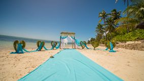 A wedding arch decorated with flowers and large wind-developing fabrics on a tropical beach. Philippines. Bohol. A wedding arch decorated with flowers and large Stock Photos