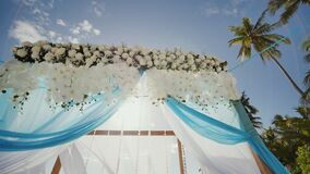 A wedding arch decorated with flowers and large wind-developing fabrics on a tropical beach. Shooting in motion. A wedding arch decorated with flowers and large stock video