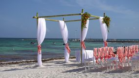 Wedding arch decorated with flowers and large wind-developing fabrics on tropical beach. Turquoise water of the. Caribbean Sea. Riviera Maya Mexico stock video