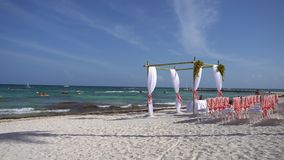 Wedding arch decorated with flowers and large wind-developing fabrics on tropical beach. Turquoise water of the. Caribbean Sea. Riviera Maya Mexico stock video footage