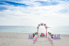 Wedding arch decorated with flowers on tropical beach, outd Stock Photos