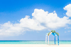 Wedding arch decorated with flowers on tropical beach, outd Royalty Free Stock Images