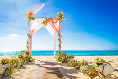 Wedding arch decorated with flowers on tropical sand beach, outd. Oor beach wedding setup Royalty Free Stock Photos