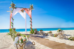 Wedding arch decorated with flowers on tropical sand beach, outd Stock Photo