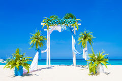 Wedding arch decorated with flowers on tropical sand beach, outd Stock Images