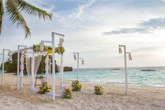 Wedding arch decorated with flowers on tropical sand beach, outd. Wedding arch - tent - decorated with flowers on beach, tropical wedding ceremony set up Royalty Free Stock Images