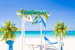 Wedding arch decorated with flowers on tropical sand beach, outd Royalty Free Stock Photos