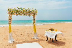 Wedding arch decorated with flowers on a tropical sand beach. Outdoor beach wedding setup. Wedding arch decorated with white and yellow flowers on a tropical Stock Photos