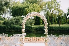 Wedding arch decorated with flowers, white and pink roses. With vintage chairs on a pond background in the sunny summer. Wedding arch decorated with flowers Royalty Free Stock Photography
