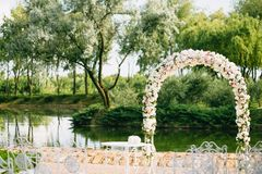 Wedding arch decorated with flowers, white and pink roses. With vintage chairs on a pond background in the sunny summer. Wedding arch decorated with flowers Stock Photo