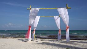 Wedding arch decorated with large wind-developing fabrics on tropical beach. Turquoise water of the Caribbean Sea. Riviera Maya Mexico stock footage