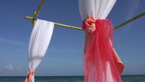 Wedding arch decorated with large wind-developing fabrics on tropical beach. Turquoise water of the Caribbean Sea. Riviera Maya Mexico stock video