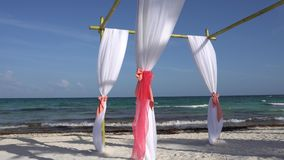Wedding arch decorated with large wind-developing fabrics on tropical beach. Turquoise water of the Caribbean Sea. Riviera Maya Mexico stock video footage