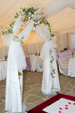 Wedding arch decorated with veil and flowers. Stock Photos