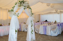 Wedding arch decorated with veil and flowers. Royalty Free Stock Photography