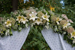 Wedding arch decorated with white flowers lilies. In a summer park Stock Photography