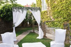 Wedding arch decorated with white material and a lot of greenery. The beautiful platform for a wedding ceremony under the open sky. Chairs on a green grass Stock Photography