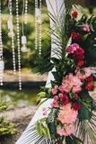 Wedding arch decoration close-up. Flower bouquets of palm leaves, pink and red roses, light bulbs and crystals stock image