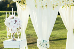 Wedding arch with flowers and сandle decoration on sunny day in ceremony place Royalty Free Stock Images