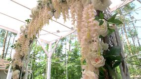 Wedding arch with flowers. Light-colored roses and leaves. Holiday of unity and love stock video footage