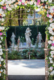 Wedding arch with flowers outdoors. Beautiful wedding set up. Wedding ceremony in the garden with sculptures and. Fountain. Part of the festive decor, floral Royalty Free Stock Photo
