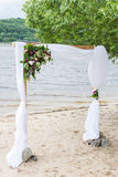 A wedding arch with greenery, peonies, and white material. Royalty Free Stock Images