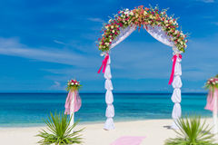 Wedding arch and set up on beach, tropical outdoor wedding. Wedding arch, cabana, gazebo on tropical beach decorated with flowers, beach wedding decoration Royalty Free Stock Photos