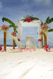 Wedding arch and set up with flowers on tropical beach Stock Photos