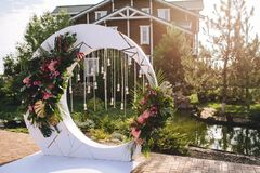 Wedding arch on the territory of hotel in the form of a white circle with flowers, leaves of palm trees with light bulbs and cryst. The Wedding arch on the Stock Images