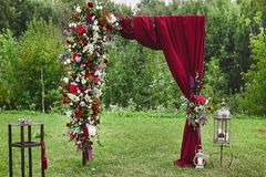 Wedding arch with vinous curtain and fresh flowers outdoors - wedding decoration.  Royalty Free Stock Photos