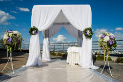 Wedding arch. White wedding arch decorated with flowers outdoor Stock Photography
