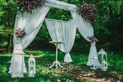 Wedding arch with white fabrics and flowers and small table in the forest. Beautiful wedding decorations outdoors. Candles and stock photos