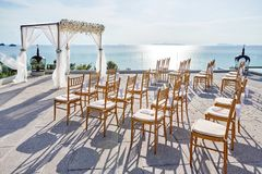 Wedding arches, flowers, floral decoration, ocean with reflection background. The gold chairs with cones of roses Stock Photography