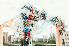 Wedding archway with flowers arranged in city for a wedding cere Stock Photos