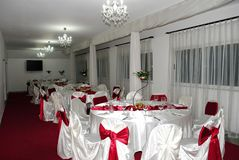 Wedding arrangement with beautiful chandelier and white and red chairs royalty free stock photo